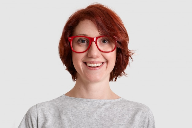 Close up shot of smiling glad woman with short hairstyle, wears red rimed spectacles, dressed casually, isolated over white wall, expresses positive feelings. people and beauty concept.