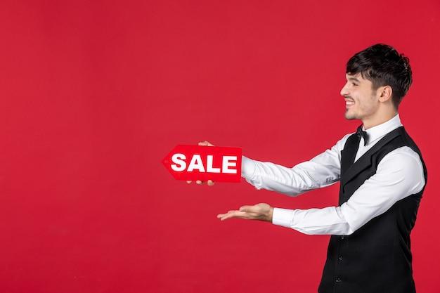 Chiuda sul colpo del cameriere sorridente del ragazzo in un'uniforme con la farfalla sul collo che mostra l'icona di vendita che indica qualcosa sul lato destro su fondo rosso isolato