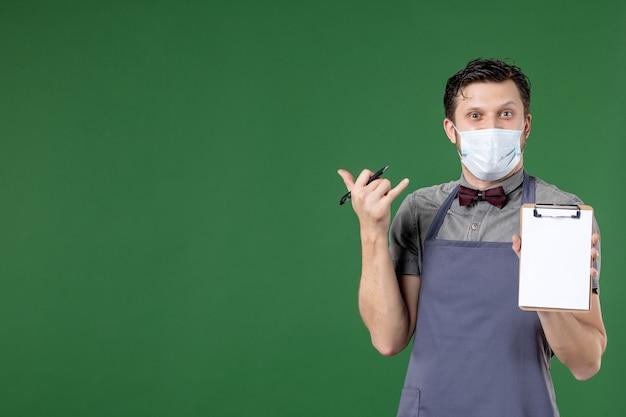 Immagine ravvicinata di un cameriere maschio sorridente in uniforme con maschera medica e con in mano il libro degli ordini su sfondo verde
