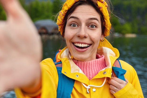 Close up shot of smiling woman stretches hand for making selfie wears yellow headband and raincoat breathes fresh air, stands against river