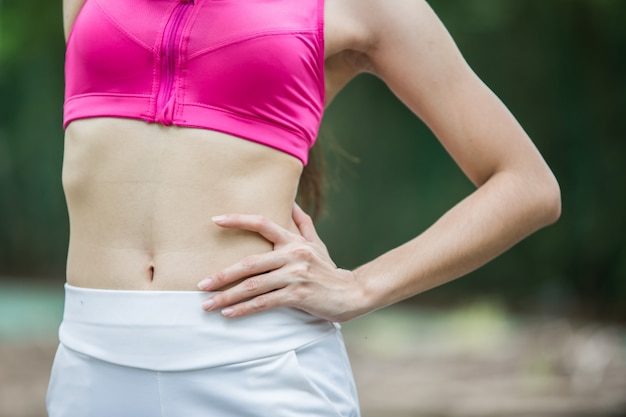 Close up shot of sport woman with her six pack muscle in sportswear outdoors at the park
