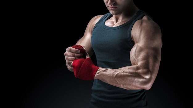 Close-up shot of strong man wrap hands on black background man is wrapping hands with red boxing wraps isolated on black background