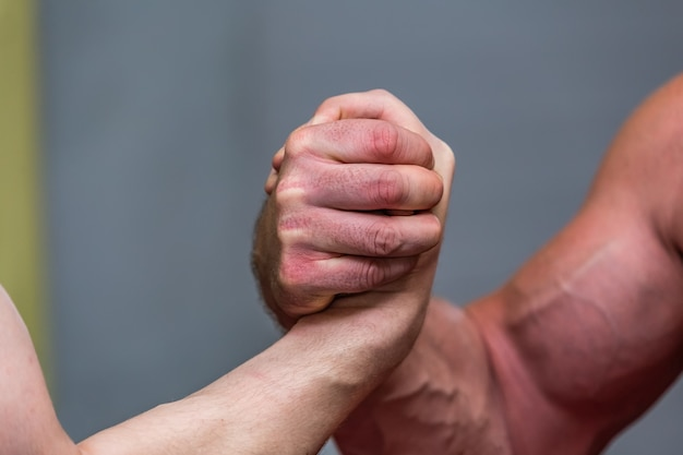 Primo piano dei muscoli di un uomo forte durante un combattimento di braccio di ferro