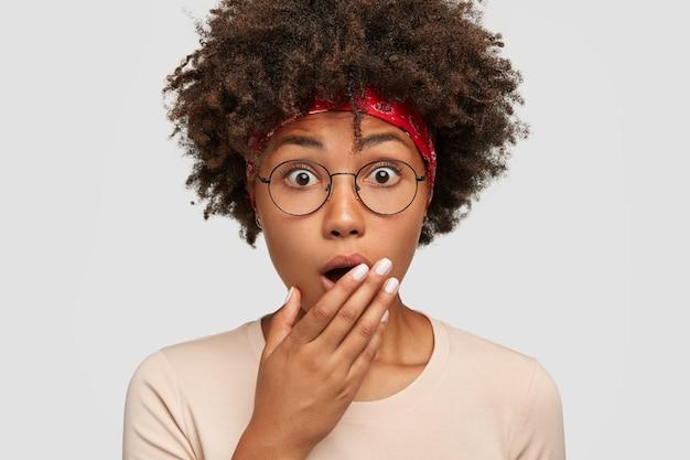 Immagine ravvicinata di stupefatta giovane donna afroamericana copre la bocca con espressione spaventata