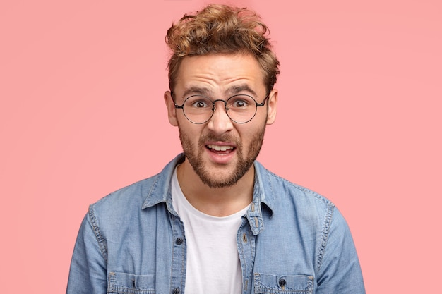 Immagine ravvicinata di stupefatto uomo indignato con i capelli ricci, guarda disperatamente alla telecamera, indossa occhiali rotondi per una buona visione