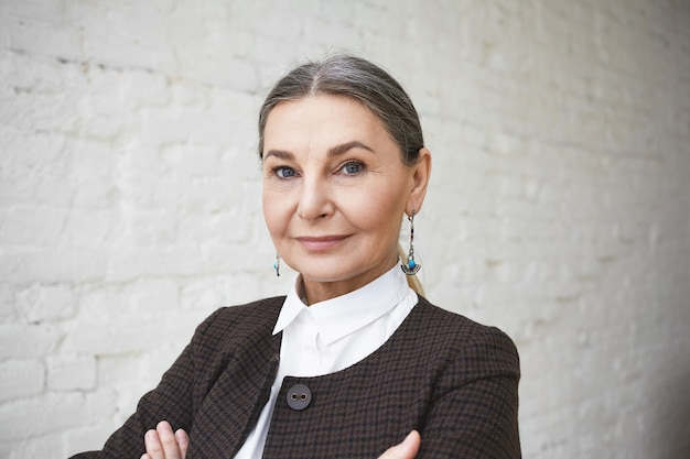 Close up shot of successful beautiful confident senior businesswoman in her fifties with gray hair and blue wise eyes posing indoors, keeping arms folded, looking with charming smile