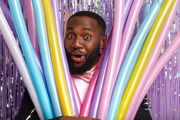 Chiuda sul colpo del ragazzo afroamericano allegro sorpreso guarda attraverso palloncini colorati modellanti, ha un'espressione gioiosa e felice. persone, etnia, divertimento, concetto di celebrazione della festa