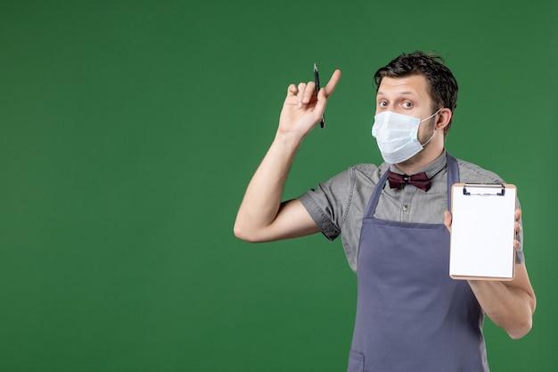 Immagine ravvicinata di un cameriere maschio sorpreso in uniforme con maschera medica e tenendo la penna del libro degli ordini rivolta verso l'alto su sfondo verde