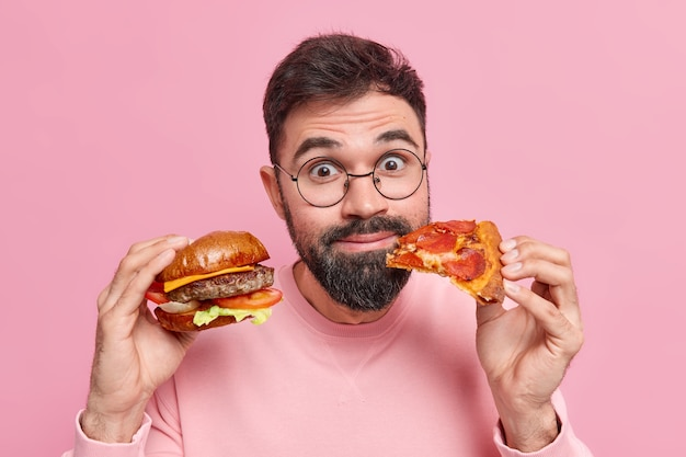 Primo piano di un uomo barbuto sorpreso e contento che tiene hamburger e un pezzo di pizza mangia cibo spazzatura non si preoccupa della salute e della nutrizione indossa occhiali maglione pulito