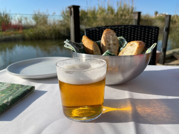 Close-up shot of a table in outdoor cafe with a glass of beer and bowl with fresh bread.