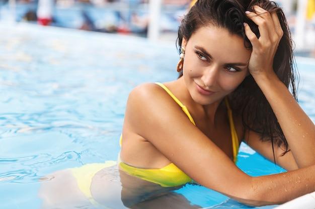 Inquadratura ravvicinata di una donna abbronzata con un tatuaggio sulla spalla, il bordo della piscina magra, voltare le spalle con un sorriso seducente e rilassato.