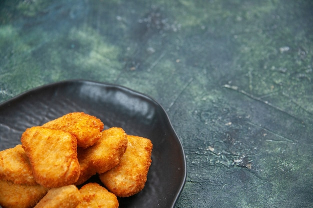 Close up shot of tasty chicken nuggets in black plate on dark surface with free space