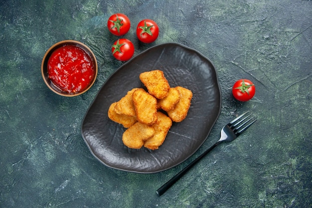 Close up shot of tasty chicken nuggets in black plate tomatoes fork on dark surface with free space