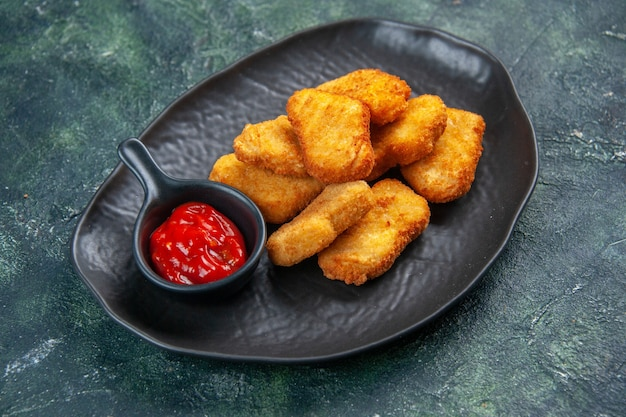Close up shot of tasty chicken nuggets and ketchup in black plate on dark surface with free space