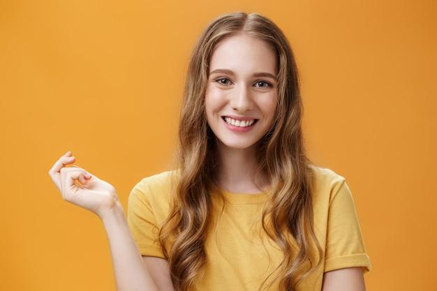 Colpo del primo piano di giovane donna alla moda spensierata e femminile tenera con bella acconciatura ondulata naturale che gesturing con la mano sullo spazio della copia sorridendo ampiamente e amichevole alla macchina fotografica contro il muro arancione.