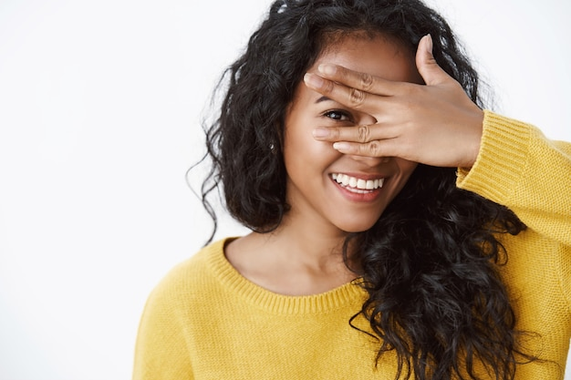 Close-up shot of tender curly-haired girl with toothy smile, holding hand on eye and peeking through fingers, express enthusiasm and joy, standing white wall
