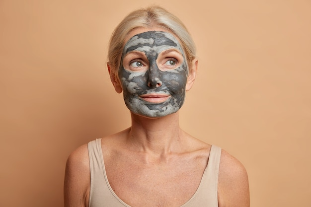 Close up shot of thoughtful european woman applies facial clay mask and looks away cares about complexion poses with bare shoulders isolated on brown wall