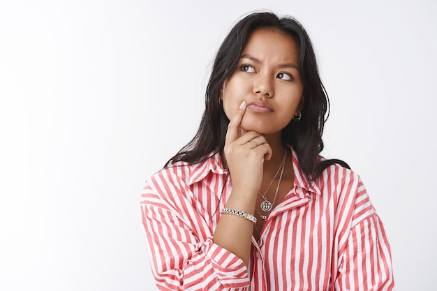 Close-up shot of thoughtful focused woman having tough problematic thought making decision in mind frowning touching lip and looking at upper left corner, thinking against white background
