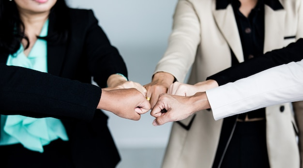 Close up shot of touching fists of unidentified unrecognizable successful female businesswoman colleagues group standing together in formal business suit encourage empower trust unity commitment.