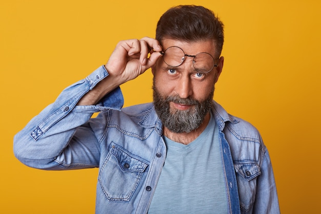 Close up shot of trendy looking middle aged hipster guy with trimmed mustache and beard posing isolated on studio wall