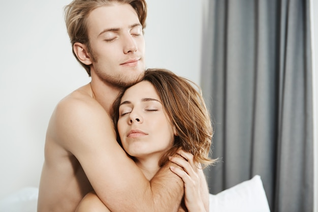 Close-up shot of two beautiful tender young adults in love, hugging in bed with closed eyes and romantic smile. couple on honeymoon enjoy first morning they woke up together