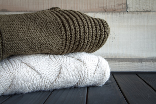 Close-up shot of two knitted from natural wool sweaters, on a black wooden table