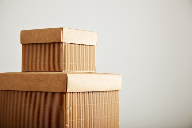 Close up shot of two similar corrugated cardboard square boxes of different sizes on top of each other isolated on white