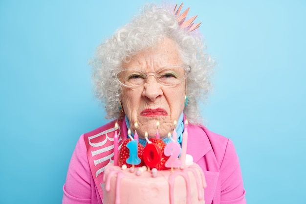 Close up shot of unhappy sulking senior woman sad life is passing and these years came so quickly poses with birhtday cake upset being forgotten by children and relatives dressed in festive outfit