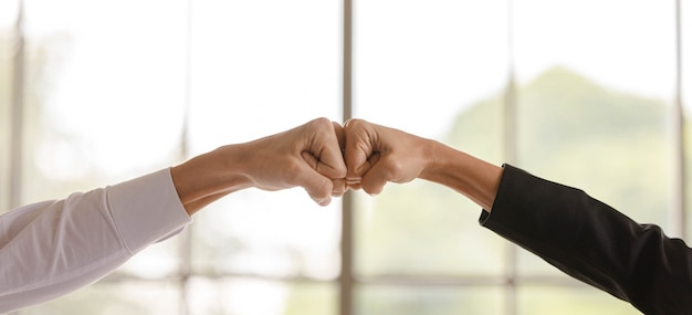 Close up shot of unrecognizable unidentified businessman and businesswoman fists bump together after final agreement achievement. selling project approval deal done in company meeting office room.