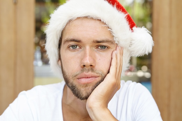 Close up shot of upset young hipster man with stubble wearing red hat with white fur holding hand on his cheek, feeling lonely and bored