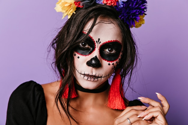 Close-up shot of vampire woman wears colorful flower wreath. inspired caucasian girl posing in masquerade costume.