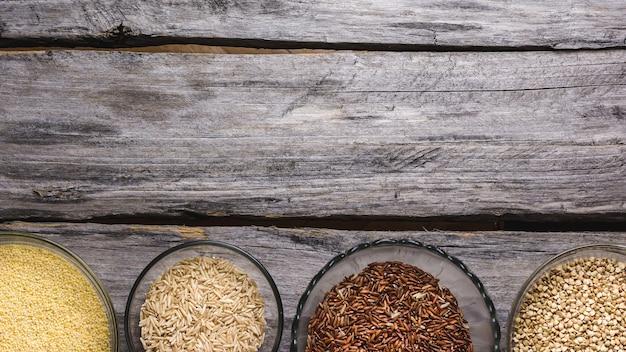 Immagine ravvicinata di vari tipi di cereali freschi in piccole ciotole di vetro