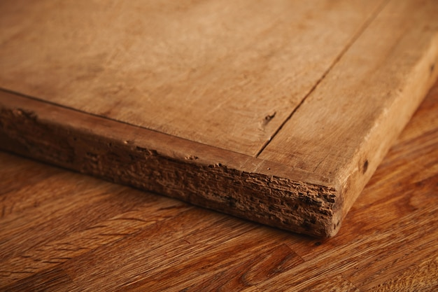 Close up shot of a very old and battered chopping board with deep cuts, pieces missing lying on a rustic wooden table