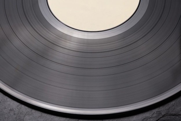 Close-up shot of vinyl record on black surface. side view