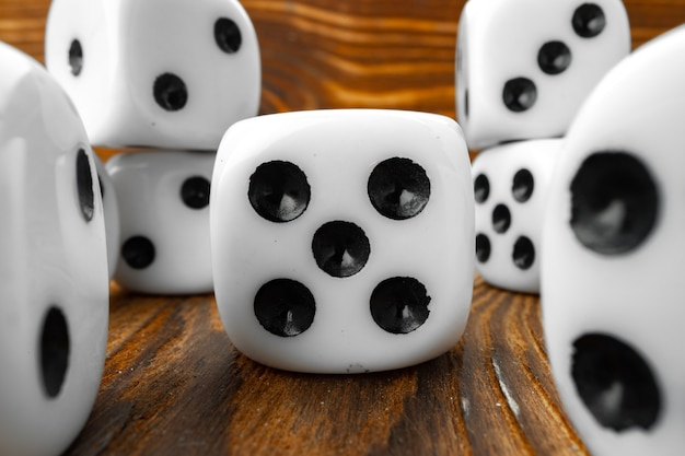 Close up shot of white dice on wooden background