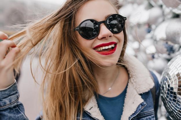 Inquadratura ravvicinata della ragazza accattivante con le labbra rosse che gioca con i suoi capelli e che ride sulla strada urbana. foto della donna abbastanza caucasica in occhiali da sole neri che gode della passeggiata di primavera.