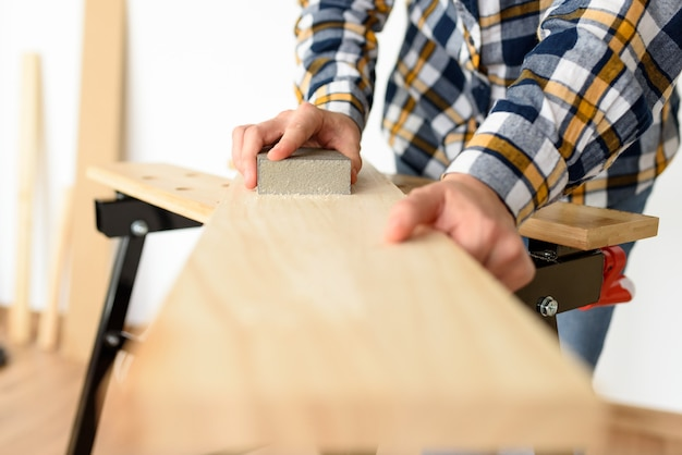 Close-up shot of a woman at home sanding a wood on a workbench. high quality photo.