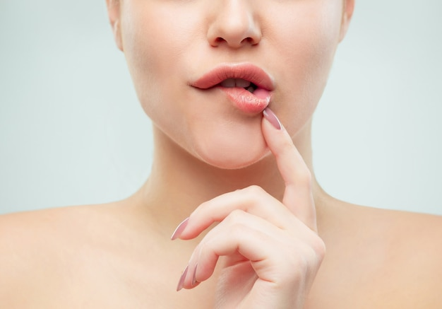The close up shot of woman lips. perfect fresh skin. pure beauty model. youth and skin care concept