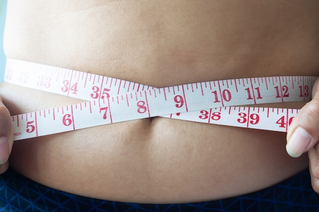 Close up shot of woman measuring waist, dieting concept