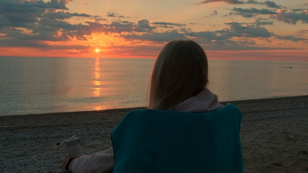 Close-up shot of woman sitting on camping chair and drinking coffee. relaxing and enjoying nature. admiring sunrise on the sea.