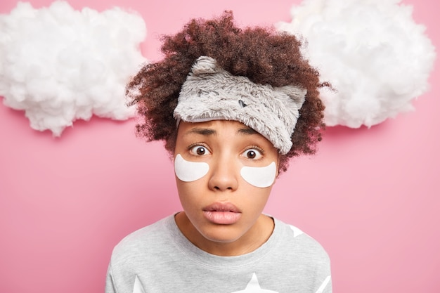 Il primo colpo di donna guarda sorprendentemente alla telecamera indossa sleepmask applica le patch sotto gli occhi per ridurre le rughe vestito in pigiama isolato sopra il muro rosa