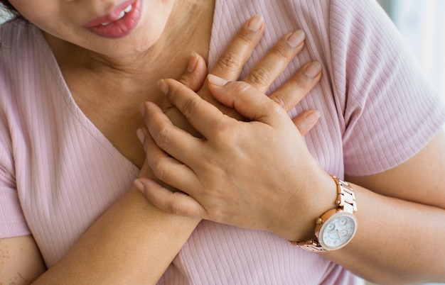 Close up shot of woman use hand to hole on her chest with pain and suffer face from heart disease. concept of st elevated myocardial infarction.