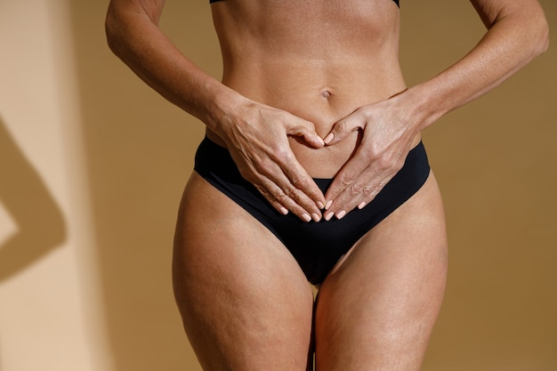 Close up shot of womans hands forming a heart symbol on belly perfect fit body of mature woman in