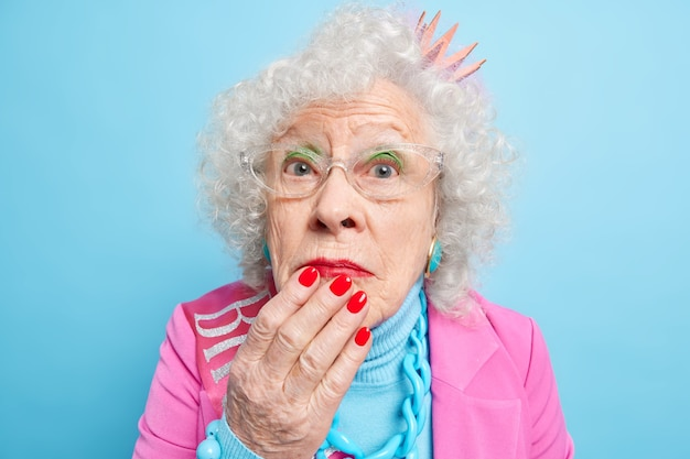 Close up shot of wondered grey haired retired woman keeps hand on chin looks surprisingly