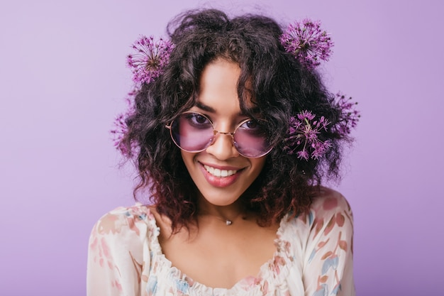 Close-up shot of wonderful female model in stylish sunglasses fooling around. indoor portrait of winsome african girl with purple flowers in black hair.