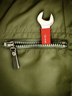 Close-up shot of wrench in a pocket of green jacket