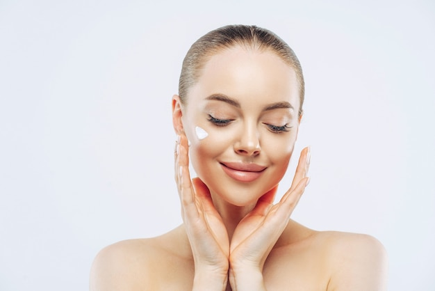 Close up shot of young adult woman with naked shoulders applies nourishing moisturising cream for soft pure skin, has tender expression, isolated on white wall. beauty, cosmetology concept