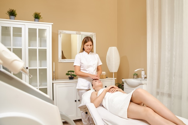 Close up shot of young female masseur making massage on the face for young pretty female client in the spa salon