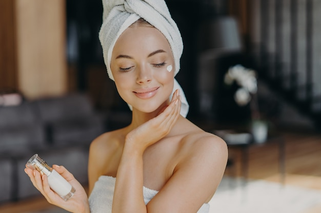 Close up shot of young feminine lady applies face lotion, wears wrapped towel on head, has bare shoulders, smiles with satisfaction, uses cosmetic product. natural beauty and cosmetology concept