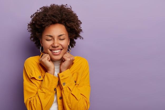 Immagine ravvicinata di giovane donna con acconciatura afro sorride con gioia, immagina qualcosa di piacevole, indossa una camicia gialla alla moda, isolata sopra il muro viola